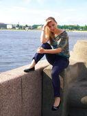 Beautiful girl sitting on a granite embankment. — Stock Photo