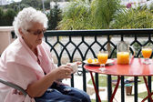 Mature lady sitting on a balcony drinking orange juice — Stock Photo