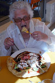 A senior lady eating a crepe — Stock Photo