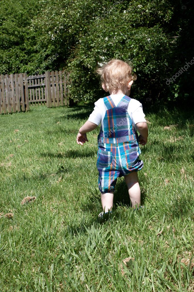 A toddler walking in the grass facing away from the camera — Stock Photo #11632273