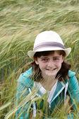 En ung flicka som gömmer sig i ett majsfält — Stockfoto