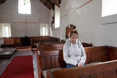 A woman sitting in an empty church praying — Stockfoto