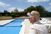 A senior lady at the outdoor pool side — Stock Photo