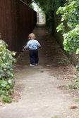 A baby boy walking down a lane — Stock Photo
