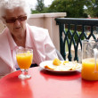 A senior woman with fresh orange juice — Stock Photo