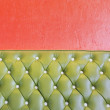 Green leather of vintage luxury armchair and orange wall - Stock Photo