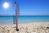 Thermometer on a beach shows high temperatures — Stock Photo