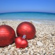 Christmas balls on the beach - Stock Photo