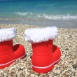 Santa Claus boots on the beach - Stock Photo