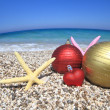Christmas ornaments on the beach - Stock Photo