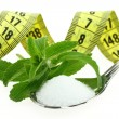 Fresh Stevia Rebaudiana, sugar in a spoon and measuring tape — Stock Photo #12298844