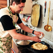 Man cooking at his kitchen eastern cuisine — Stock Photo