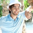 Royalty-Free Stock Photo: Young man wearing hat and casual clothes in sunny day. Leaning o