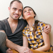 Attractive young adult couple sitting close on floor in home smi — Stock Photo #10947609