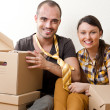 Young Couple with boxes in the new apartment sitting on floor an - Stock Photo
