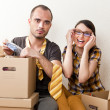 Young Couple with boxes in the new apartment sitting on floor an — Stock Photo #10947670