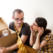 Young Couple with boxes in the new apartment sitting on floor an — Stock Photo #10947686