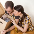 Stock Photo: Young Couple with boxes in the new apartment sitting on floor an