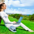 Pretty woman sitting by tree with laptop computer — Stock Photo #10948293