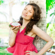 Portrait of young pretty woman wearing bright pink dress eating - Foto de Stock