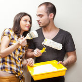 Happy smiling couple painting interior wall of home and having f — Stock Photo