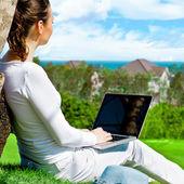 Jonge vrouw met laptop onder boom zitten en dromen. idyllische — Stockfoto