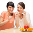 Cheerful Women eating fruits and drinking red wine — Stock Photo