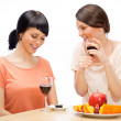 Cheerful Women eating fruits and drinking red wine — Stock Photo #10995397