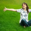 Full length of pretty young woman resting on grass and smiling. — Stock Photo #10995403