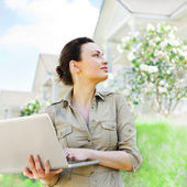 Young pretty female realty agent with laptop presenting beautifu — Stock Photo