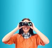 Woman looking through binoculars isolated on blue — Stock Photo