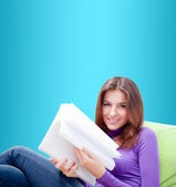 Young adult woman writing in her copybook while sitting on a lar — Stock Photo