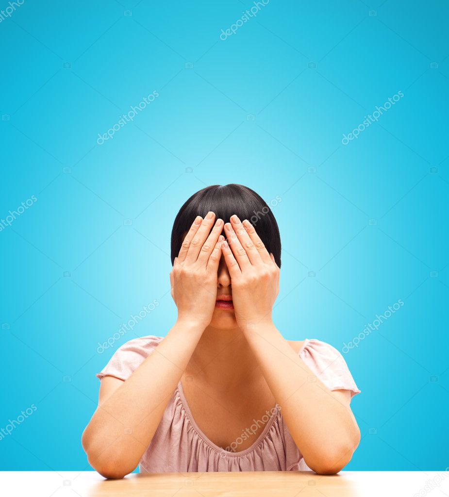 Young woman sitting isolated against blue background with eyes closed by her hands — Stock Photo #11093161