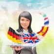 Stock Photo: Young womwearing suit holding tablet computer. Flags of Europ