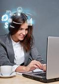 她的笔记本电脑和带有不同的图标上工作的年轻商业女士 — 图库照片