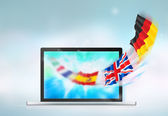 Opened laptop with european flags flying from the screen — Stock Photo