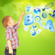 Happy little boy pointing up. Icons of different lessons flying near him. Primary education — Stock Photo