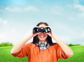 Woman looking through binoculars at summer park — Stock Photo