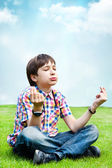Photo of adorable young wise boy sitting on the grass at his bac — Stock Photo