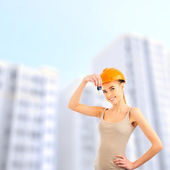 Pretty woman presenting new apartment in modern house building. — Stock Photo