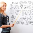 Portrait of young teacher pointing on white marker board in mode — Stock Photo