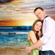 Foto Stock: Portrait of young couple in love embracing at beach and enjoying