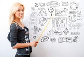 Portrait of young teacher pointing on white marker board in mode — Stockfoto