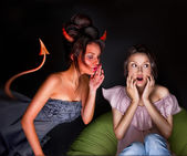 Young woman sitting at home and seductive devil coming to her an — Stock Photo