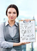 Business woman holding papers with sketches for her business — Stock Photo