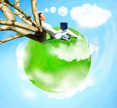 Young woman sitting under tree at her own small planet flying at — Stock Photo