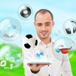 Adult handsome man holding tablet computer. Icons of different object are flying around. — Stock Photo #11678817