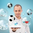 Adult handsome man holding tablet computer. Icons of different object are flying around. — Stock Photo #11678823