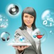 Pretty business woman holding tablet computer and different objects are flying from touch screen — Stock Photo #11678832