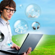 Handsome man holding laptop. Different objects are flying — Stock Photo